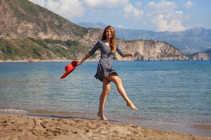 Beautiful woman jumping on a sand beach